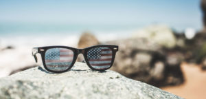 sunglasses with american flag on the lenses sitting on a rock with the beach in the backdrop