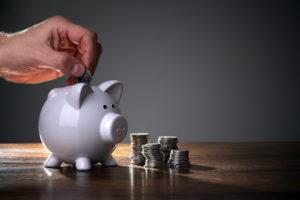 man putting money into a piggy bank